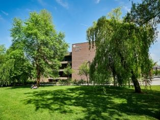 Durham University's Bill Bryson Library in the sunshine with trees