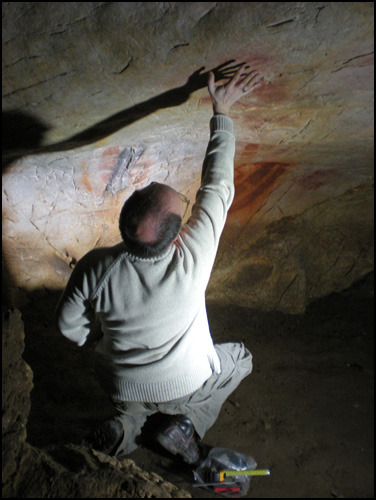 Positioning of a stencil in El Castillo (Cantabria, Spain). Note the importance of shadow of the stenciled person's arm. Photo Becky Harrison and courtesy Gobierno de Cantabria.
