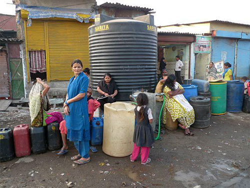 Rafinagar residents waiting at one of the temporary water storage tanks for the BMC water tanker to come and fill it.