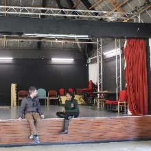 Two students sitting on the stage of Fountains Hall theatre