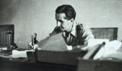 J.G. Mavrogordato, Deputy Legal Secretary and Advocate General, writing at a desk from the collection of P.P. Howell
