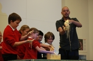 School children, with Jon Tickle, experiment with custard