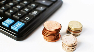 Stock image pertaining to the matter of finance, showing a calculator and some coins