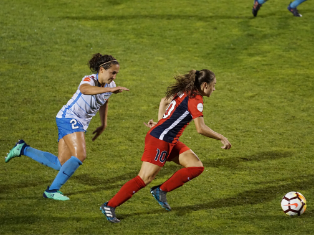 two women footballers chasing a football