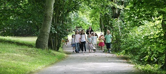 Family walks down tree lined path