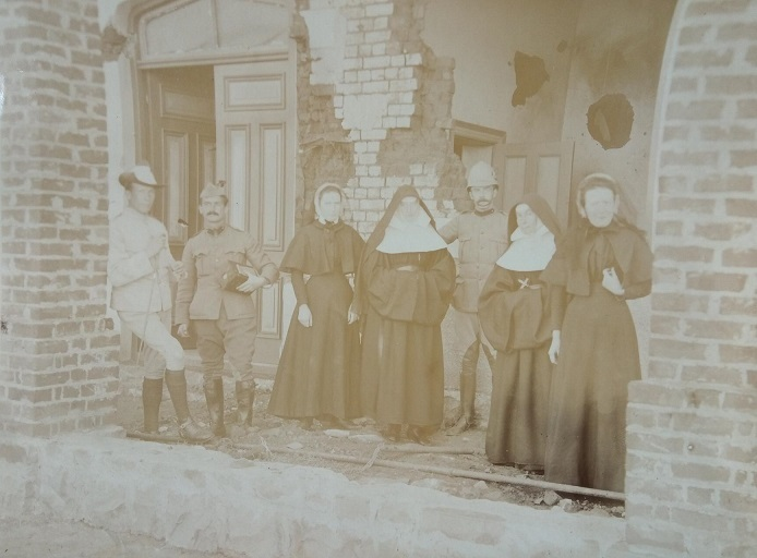 Image of a group in front of the convent at Mafeking showing the effects of a 'Long Tom' Boer 94.8lb shell, [May 1900]. Christopherson stands second from left. (J.B. Christopherson collection, Sudan Archive Durham. Reference: SAD.335/4/17)